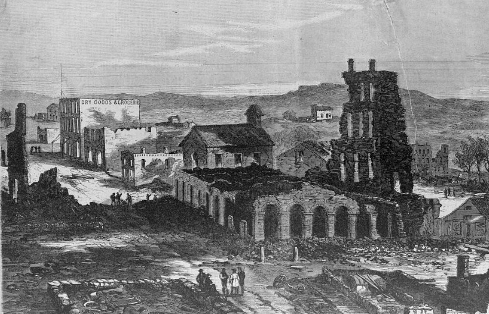 Lawrence in ruins as illustrated in Harper's Weekly. The charred remains of the Eldridge House are in the foreground.