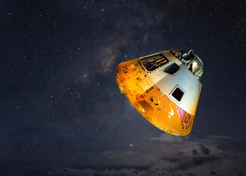 An orange and white conical craft in outer space.